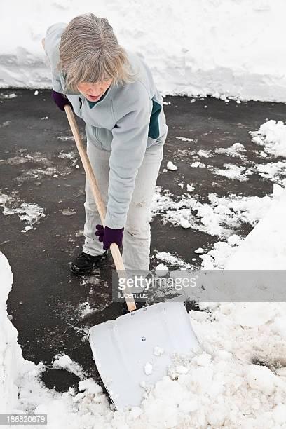 Frau ausführen Schnee mit einem großen Schneeschaufel.