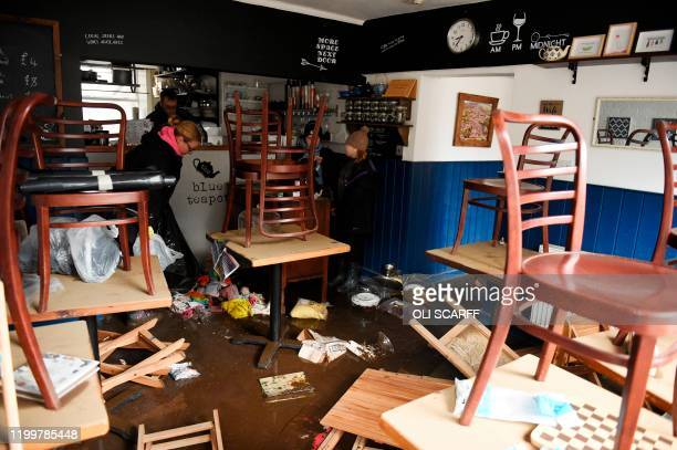 A woman clears debris inside the Blue Teapot cafe in Mytholmroyd northern England on February 10 2020 after flooding brought by Storm Ciara Storm...