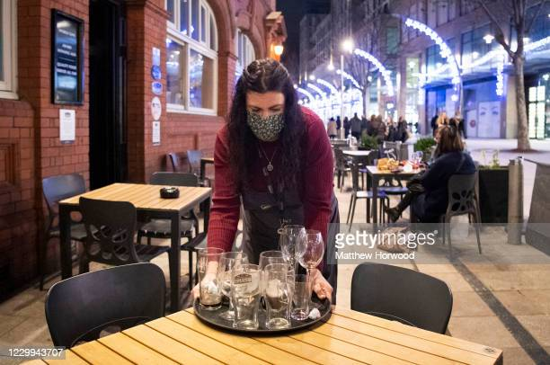 Woman clears glasses at the Duke of Wellington pub on December 4, 2020 in Cardiff, Wales. Following a firebreak period that ran from October 23 to...