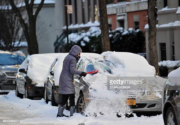 A woman clears snow off her car on East 92st Street on the east side of Manhattan January 22 2014 in New York The northeastern US shivered amid heavy...