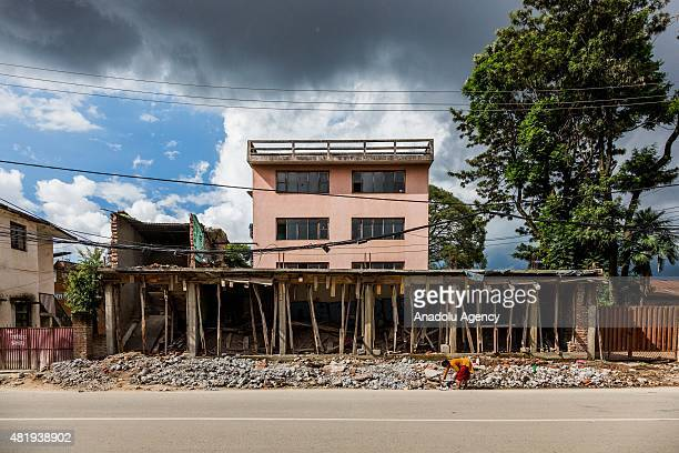 Woman clears the debris of a destroyed house from the side of the road in Kathmandu on July 25, 2015. Today marks the 3 month anniversary of the...