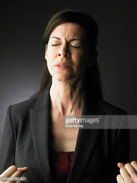 Woman clenching fists, eyes closed
