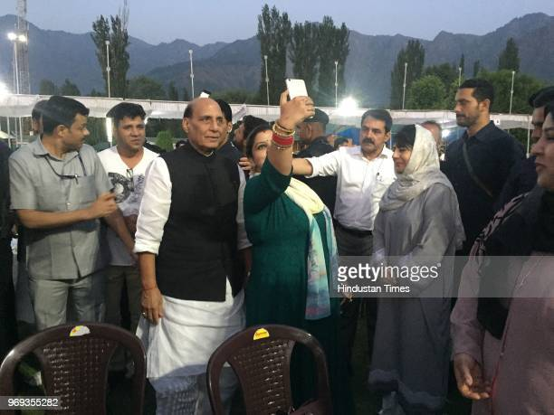 A woman clicks selfie with Union Home Minister Rajnath Singh as Jammu Kashmir Chief Minister Mehbooba Mufti looks on during an Iftar party at...