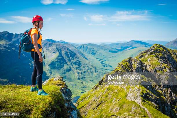 Woman climber on mountain ridge overlooking Glen Coe Highlands Scotland