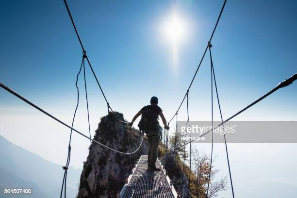 woman climber on top of the mountain at sunset - suspension bridge stock photos and pictures