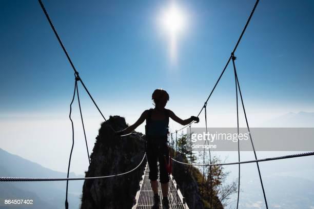 frau bergsteiger am gipfel des berges bei sonnenuntergang - hängebrücke stock-fotos und bilder