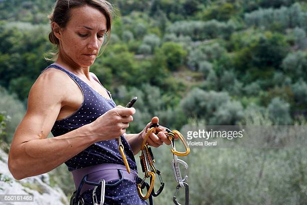 Woman climber preparing safety harness with carabinas