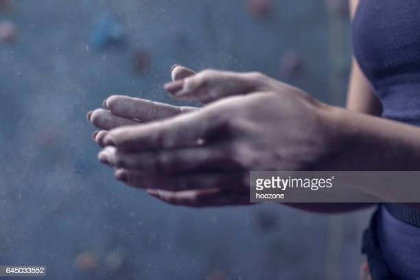 Woman climber rubbing sports chalk on hands