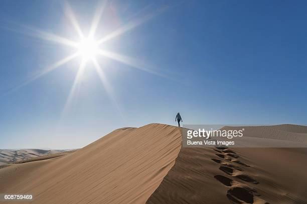 Woman climbing a giant sand dune in a desert