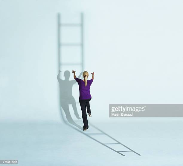 Woman climbing a ladder's shadow