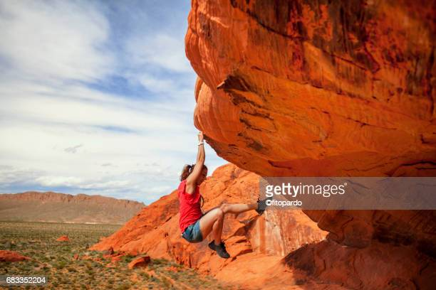 woman climbing a rock in valley of fire - free climbing stock pictures, royalty-free photos & images