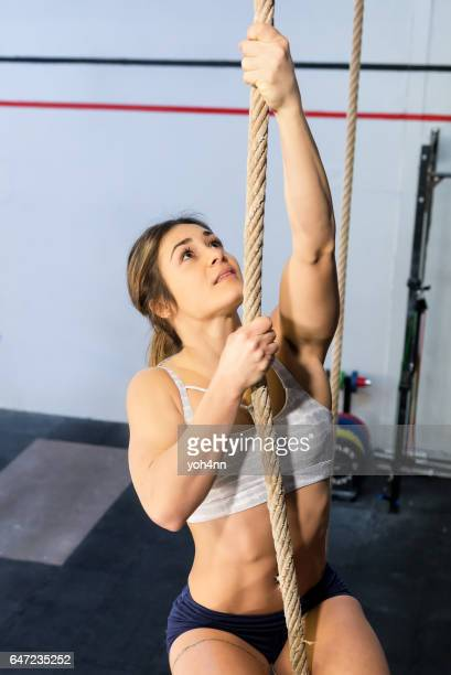 Woman climbing a rope at the health club