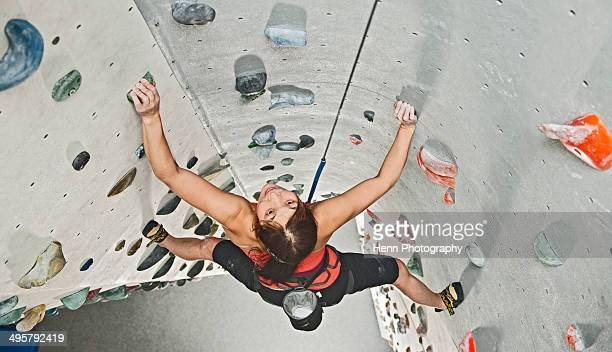Woman climbing at indoor climbing centre