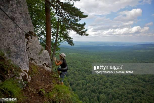 Woman climbing cliff Via ferrata, Guam gorge, Krasnodar Krai, Russia