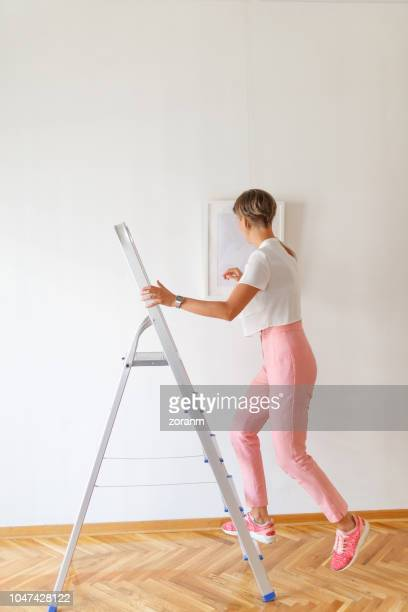 woman climbing down the ladder in art gallery - positioning stock pictures, royalty-free photos & images