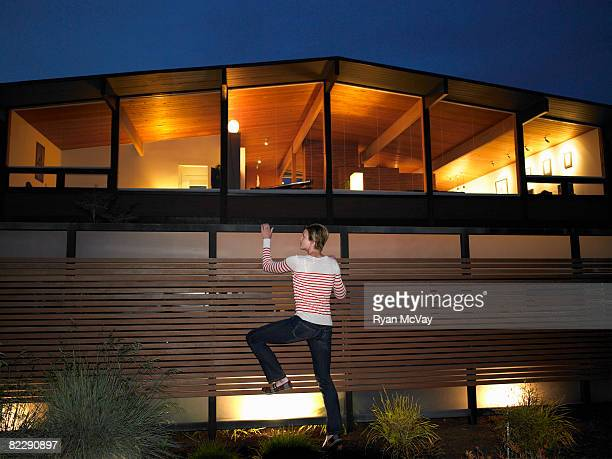 Woman climbing fence in front of house, night