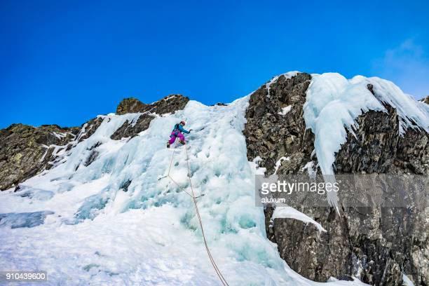 ピレネー山脈のフランスで凍った滝を登る女
