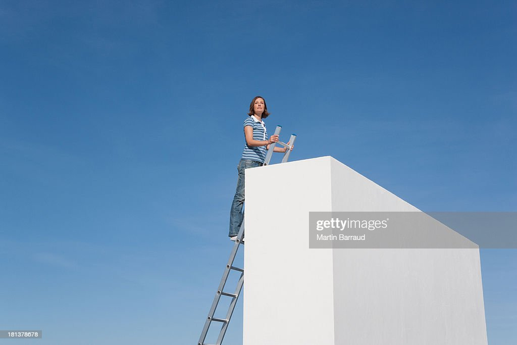 Woman climbing ladder on wall outdoors : Stock Photo