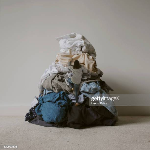 woman climbing laundry mountain - heap stock pictures, royalty-free photos & images