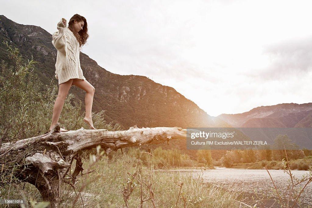 Woman climbing on log by lake : Stock Photo