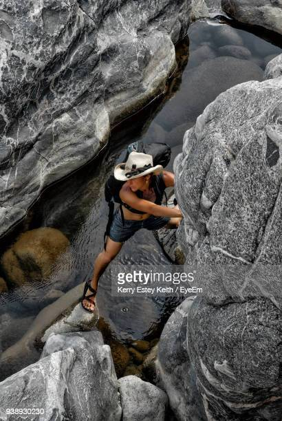 woman climbing on rock over lake - kerry estey keith stock photos and pictures