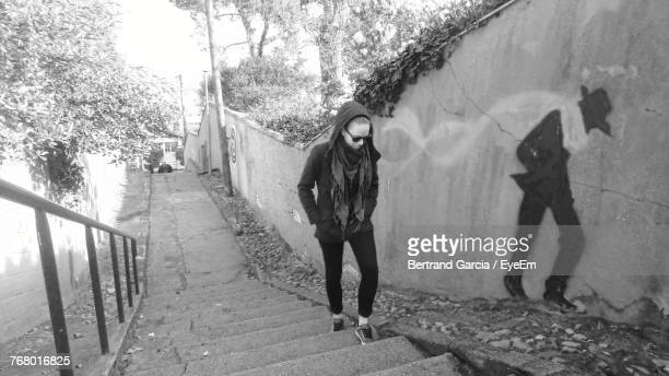 Woman Climbing On Steps While Imitating Wall Painting