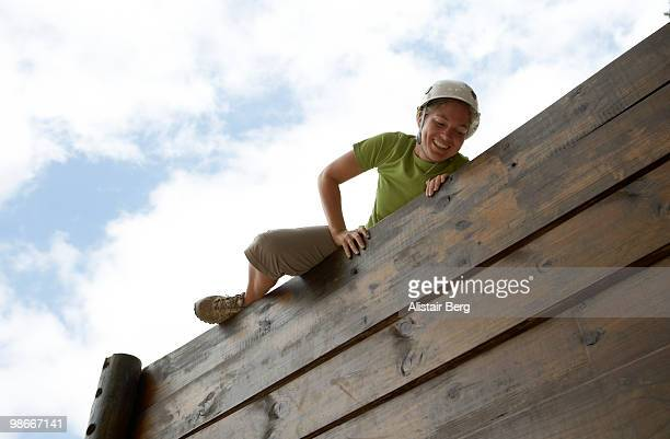 Woman climbing over obstacle course
