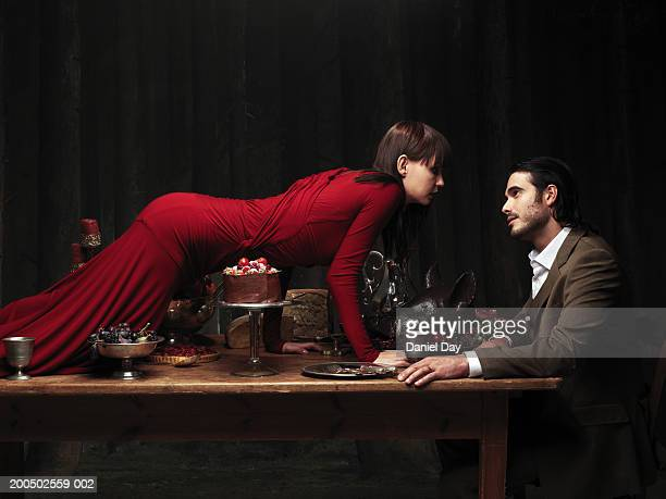 Woman climbing over table to man, side view