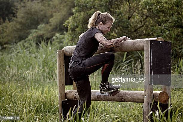 woman climbing over wooden obstacle during mud run