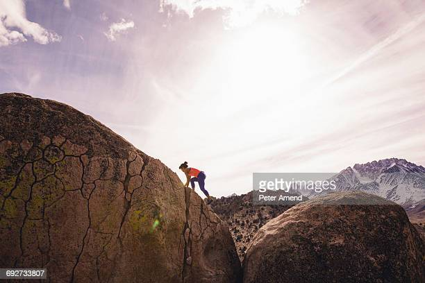 Woman climbing rock, Buttermilk Boulders, Bishop, California, USA