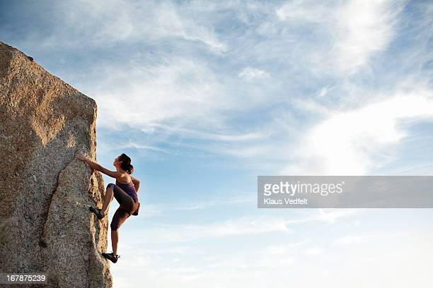 woman climbing rock side - scalare foto e immagini stock