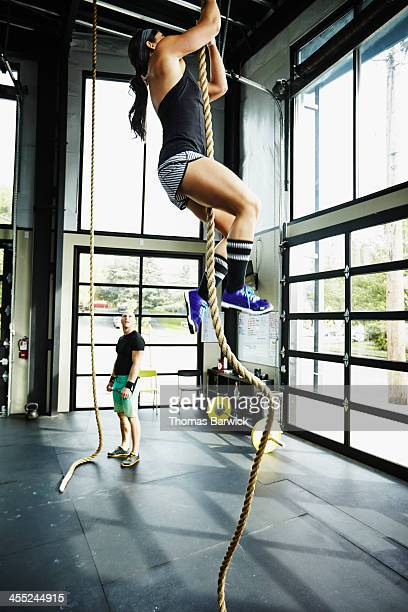 Woman climbing rope in gym gym