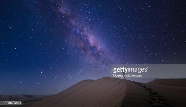 woman climbing sand dune at night - three quarter length stock pictures, royalty-free photos & images