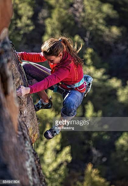 Woman climbing steep cliff, Grand Junction, Colorado, USA