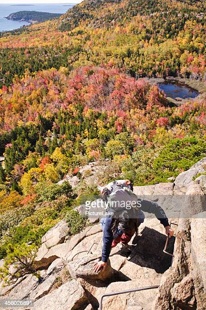 Woman climbing The Beehive, Acadia National Park, in Autumn