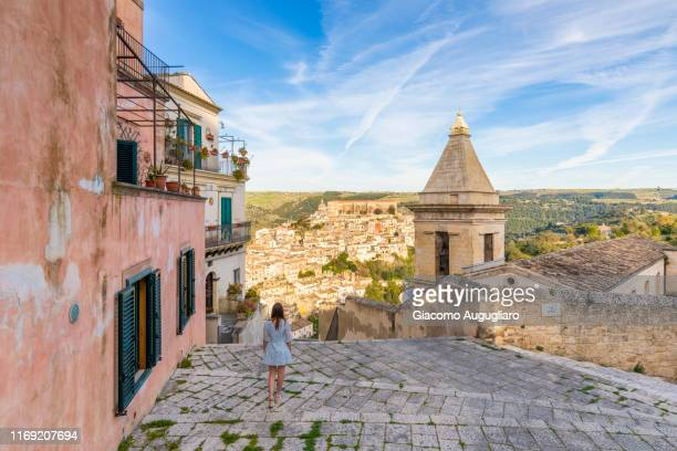 woman climbing the stairs of santa maria delle scale church, ragusa ibla in the background, ragusa, sicily, italy, europe - sicily stock pictures, royalty-free photos & images