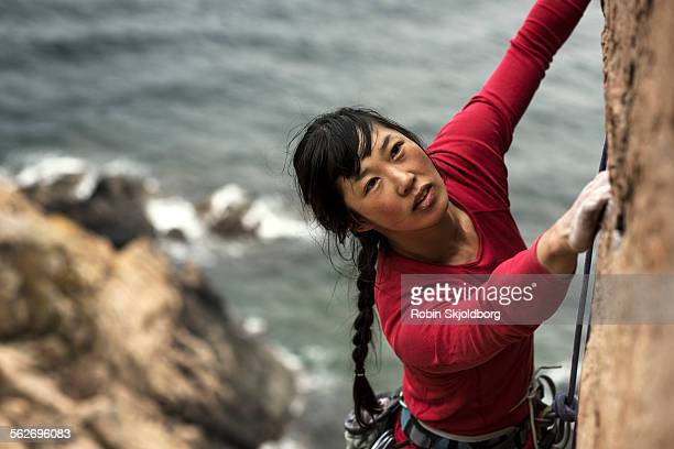 Woman climbing up cliff with ocean in background