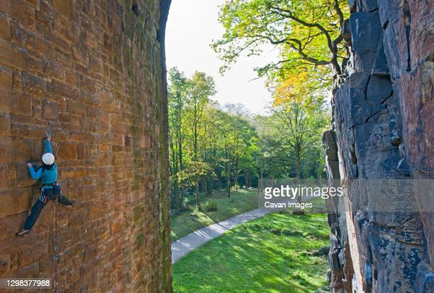 woman climbing up on man made viaduct in sheffield - sheffield stock pictures, royalty-free photos & images