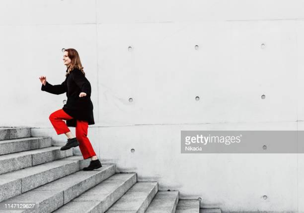 femme grimpant dans les escaliers - élevé photos et images de collection