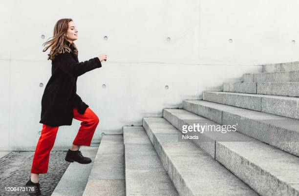 woman climbing up the stairs - steps stock pictures, royalty-free photos & images