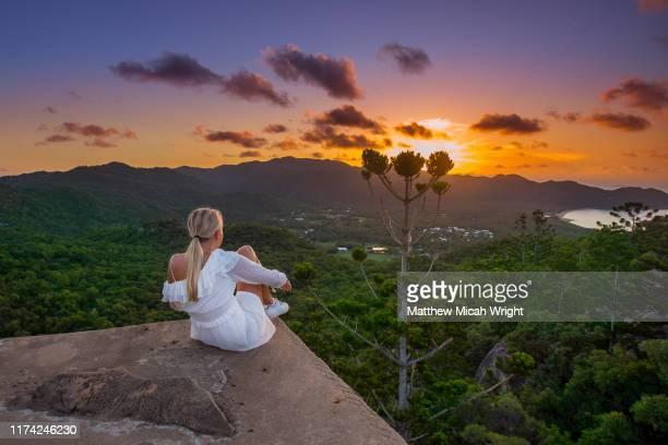a woman climbs atop a building to watch the sunset. - townsville australia fotografías e imágenes de stock