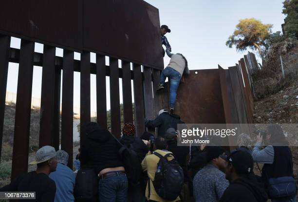 Woman climbs atop a fellow member of the migrant caravan while crossing over the U.S.-Mexico border fence on December 2, 2018 from Tijuana, Mexico....