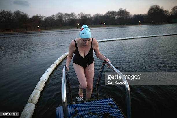 A woman climbs out of the Serpentine lake in Hyde Park after an early morning swim on December 13 2012 in London England Extremely cold conditions...