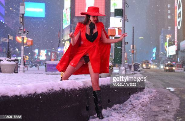 Woman climbs over snow covered wall in Time Square during a winter storm on February 1, 2021 in New York City. - A powerful winter storm is set to...