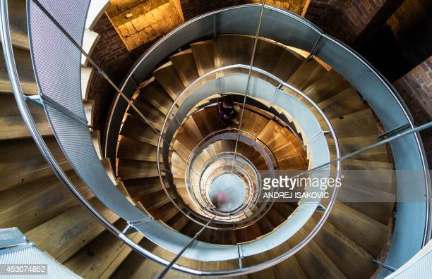 A woman climbs the spiral stairs at the Lighthouse designed by the architect Charles Rennie Mackintosh in Glasgow on August 2 2014 The Lighthouse...