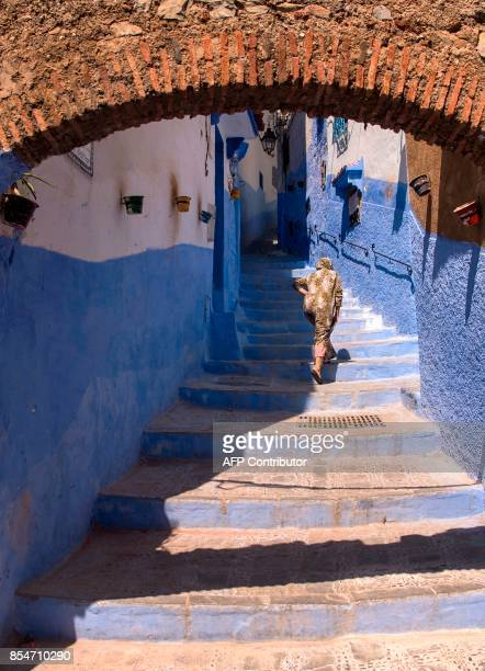 A woman climbs the stairs in the Medina of the northwestern Moroccan city of Chefchouen in the northern Rif region on September 21 2017 / AFP PHOTO /...