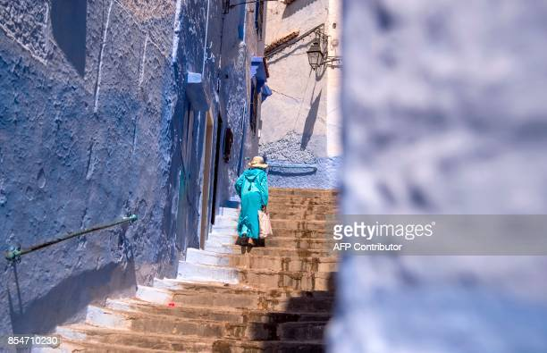 A woman climbs the steps in the Medina of the northwestern Moroccan city of Chefchouen in the northern Rif region on September 21 2017 / AFP PHOTO /...