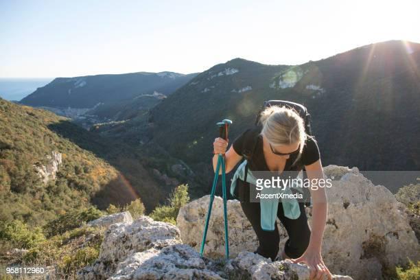 femme grimpe de roches au-dessus de la vallée et les montagnes - blonde forte poitrine photos et images de collection