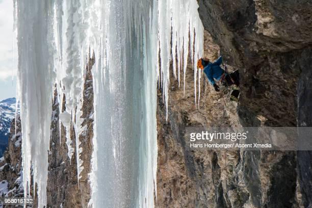 Woman climbs vertical ice pillar, above mountains