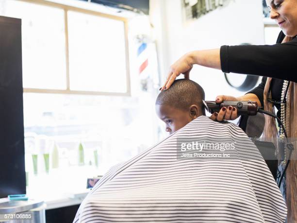 Woman clipping hair of boy in retro barbershop